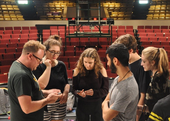 Director+Sean+Kifer+teaches+student+actors+how+to+use+a+prop.