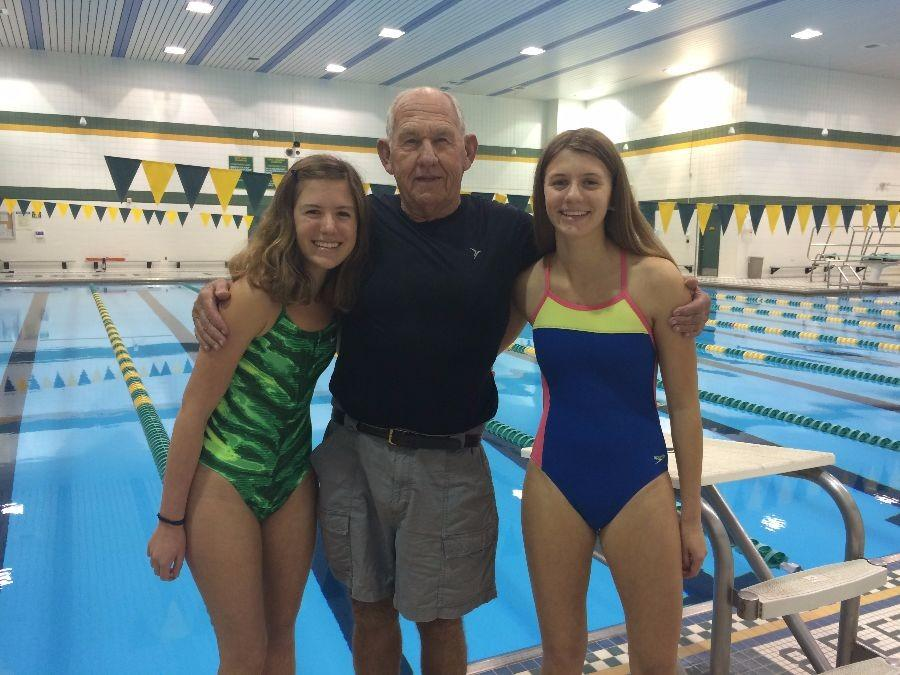 Junior Gina Peruzzi, varsity assistant swimming coach  Fred Michalik and freshman Olivia Peruzzi pose for a family photo in front of the pool.