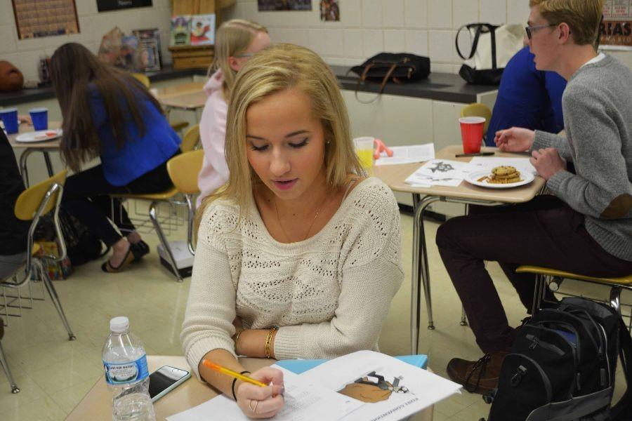 Junior Emme Kensora consults her research packet.