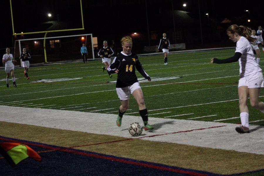 Sophomore Chloe Redeye, 14, dribbles the ball around a defender
