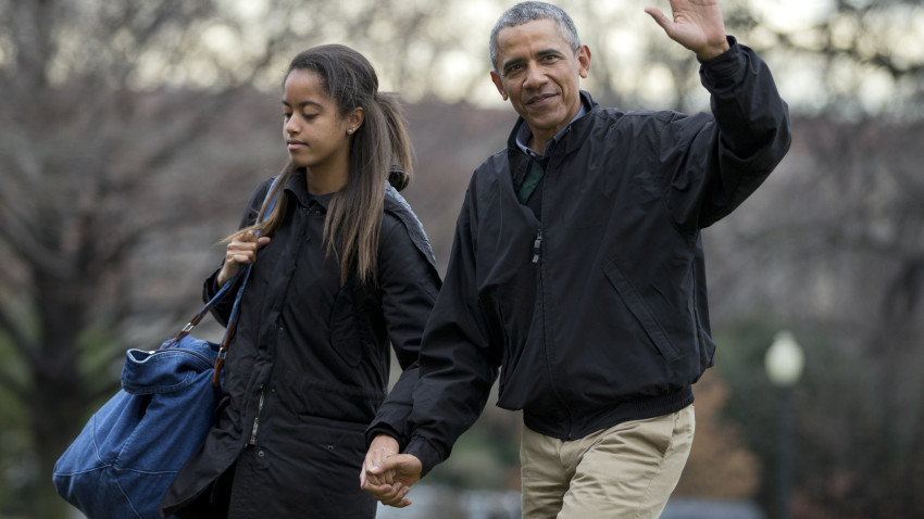 President Barack Obama, right, with his daughter Malia Obama, wave as they arrive at the White House in Washington.