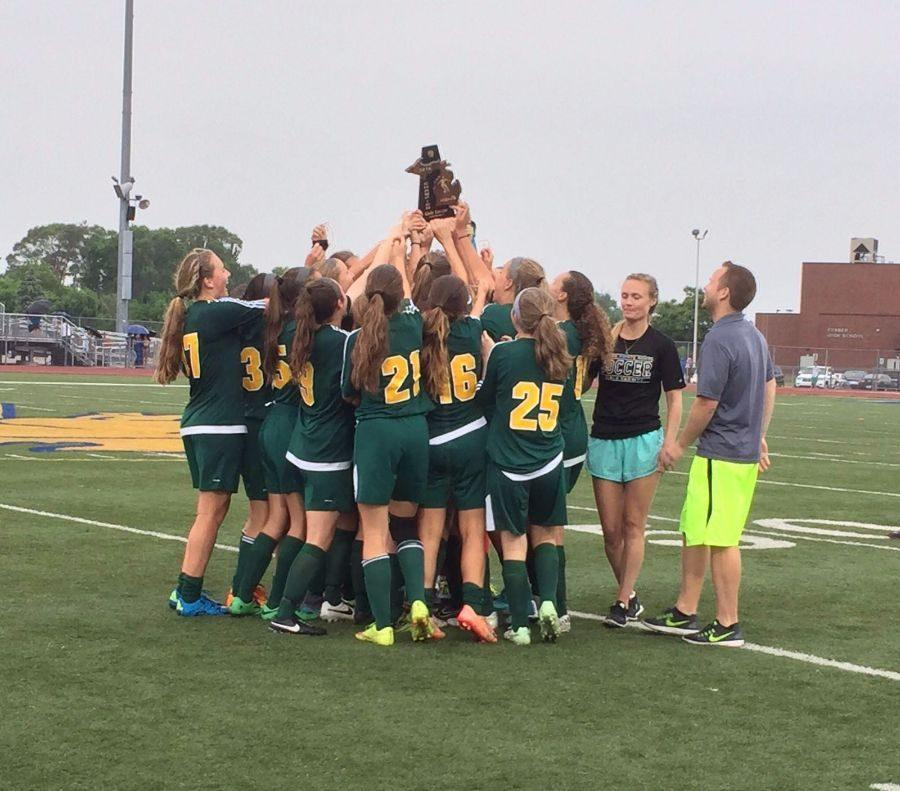 The+girls+varsity+team+hoists+up+their+district+trophy.+