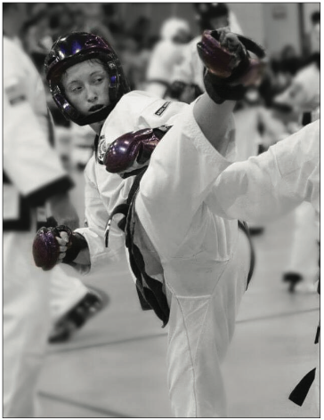 Instructor Alyssa Folkwie spars and does a hook kick.