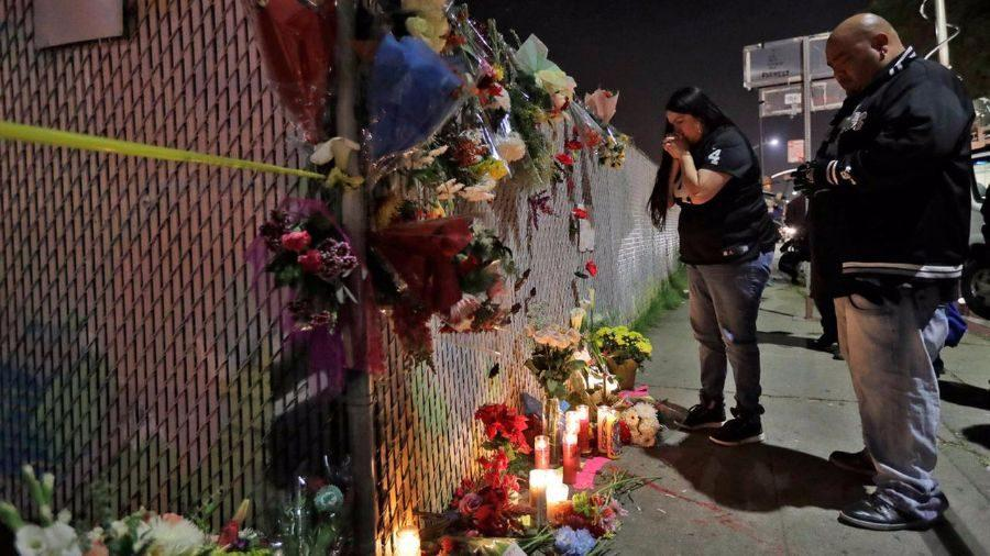 Members of the Oakland community grieve at a memorial site after the names of seven of the eight victims were released.
