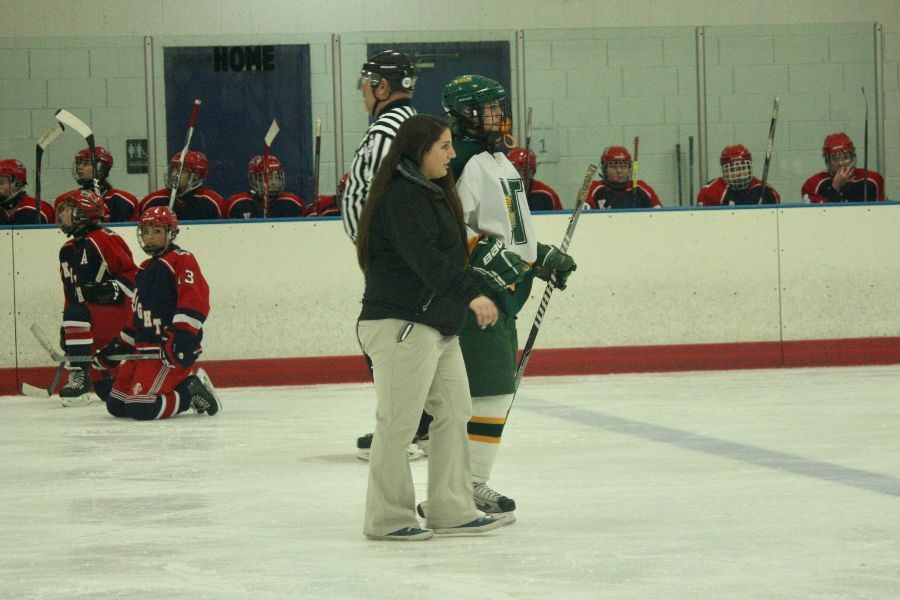 Athletic trainer Lizzy Landa helps a hockey player off the ice