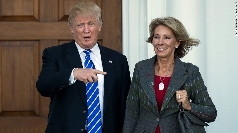 President Donald Trump poses after a meeting with Secretary of Education Betsy DeVos. DeVos was confirmed last week after a tie-breaking vote by Vice President Pence.