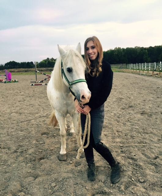 Junior Anna Elliott poses at a field with her horse, Scout.